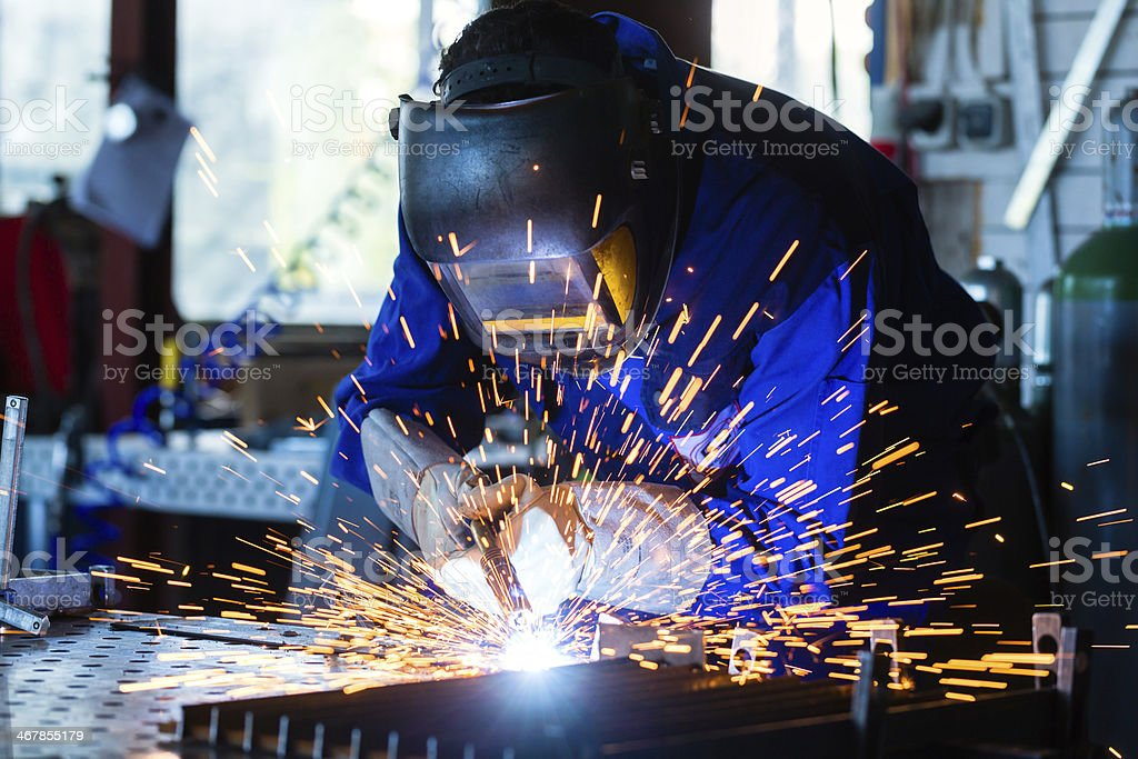 Welder welding metal in workshop with sparks stock photo