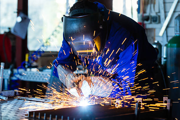 Welder welding metal in workshop with sparks Welder bonding metal with welding device in workshop, lots of sparks to be seen, he wears welding goggles metalwork stock pictures, royalty-free photos & images