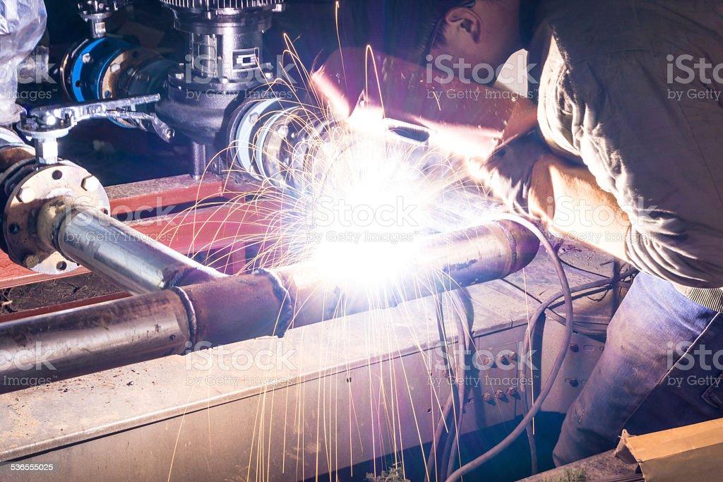 welder welding pipeline at night