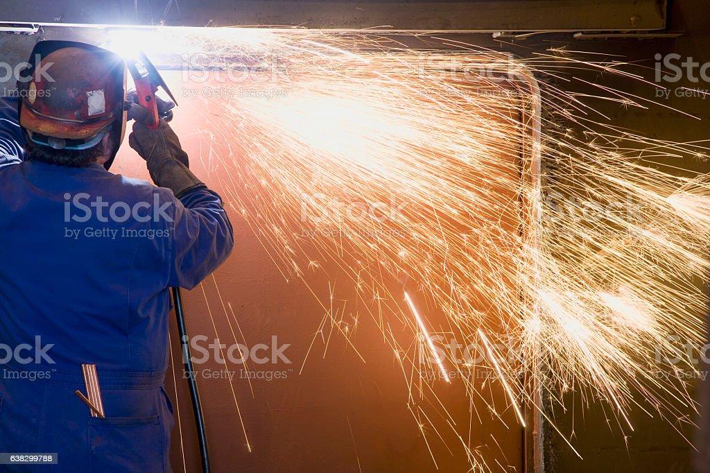 Welder welding side of boat hull in machine shop stock photo