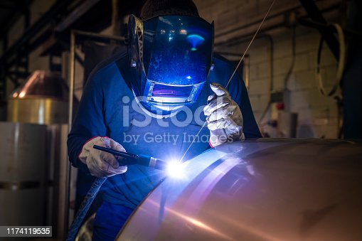 Welder welding stainless steel tank at industry workshop
