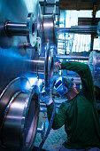 Welder welding stainless steel tank at industry workshop