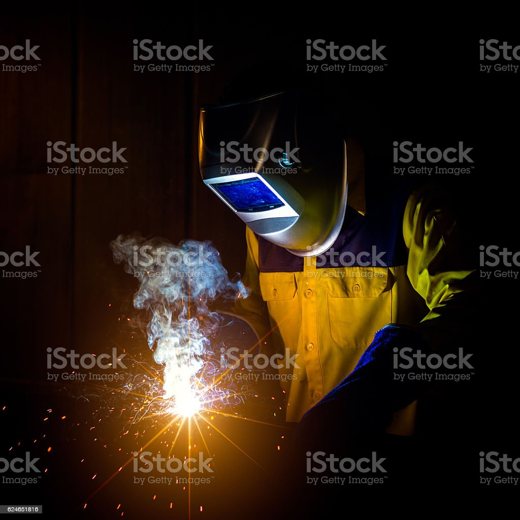 Welder with personal protective equipment and protective mask welding...