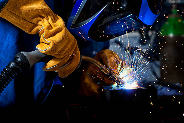 Welder with welding sparks Welder wearing gloves and mask with welding sparks. metalwork stock pictures, royalty-free photos & images