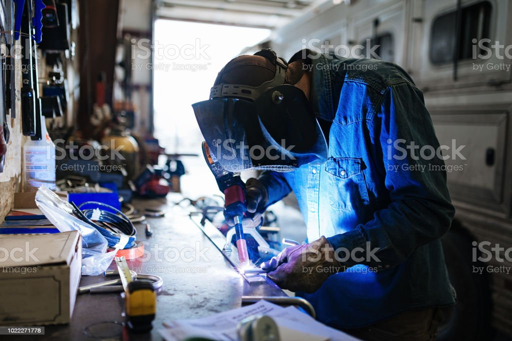 Blue collar worker doing daily work in mechanics workshop with work...