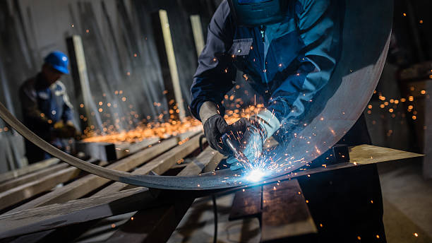 Welder working in workshop Man using welding torch to cut metal sheet in workshop. sheet metal stock pictures, royalty-free photos & images