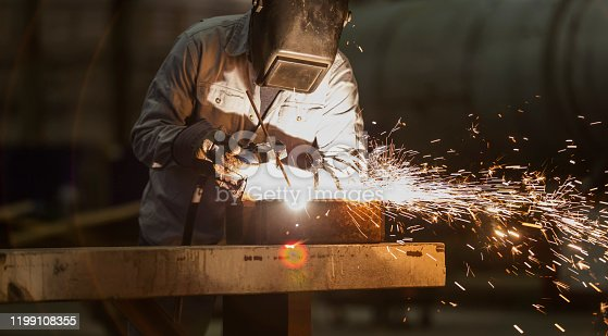 A mature man in his 50s working in a metal fabrication factory as a welder. He is covered in protective workwear, welding mask and gloves. Sparks are flying as he uses the welding torch.