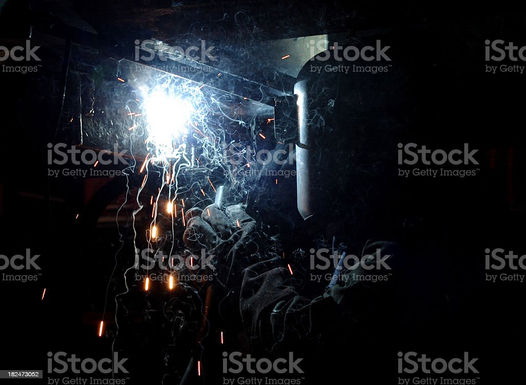 Welder working underneath machine stock photo