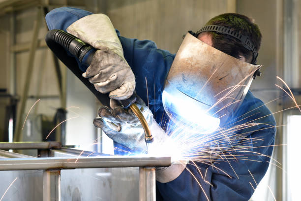 welder works in metal construction - construction and processing of steel components stock photo