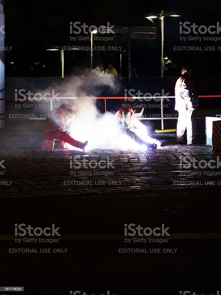 Welders repairing tramlines at night royalty-free stock photo