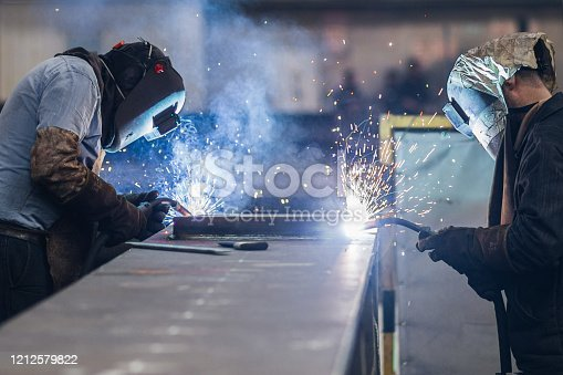 Men using welding torch to cut metal sheet in workshop.