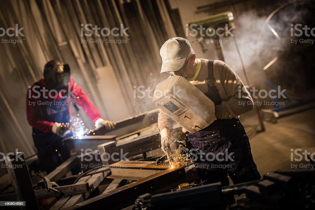 Two senior men using welding torch and welder\'s visor while welding...