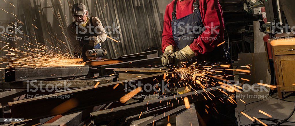Two senior men using welding torch while welding in workshop.