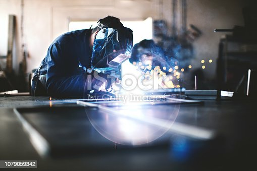 Two unrecognizable men with safety helmets welding and grinding metal together.