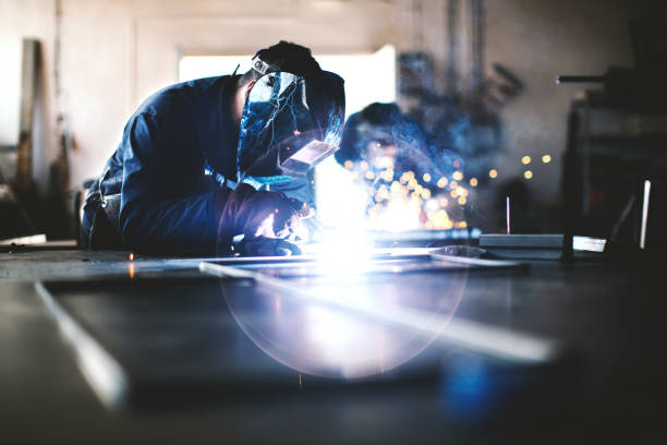 Welding and grinding. Two unrecognizable men with safety helmets welding and grinding metal together. metal worker stock pictures, royalty-free photos & images