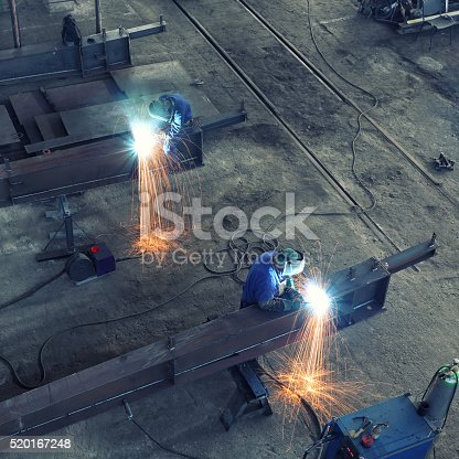 Workers with protective mask welding large steel beam, view from above. Workers can not be recognized because of the masks and equipment .
