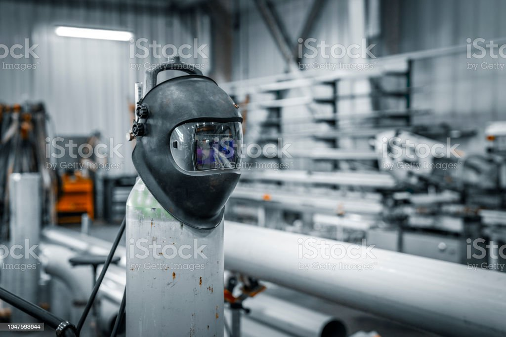 Welding mask on cylinder in factory. Interior of metal industry. It...