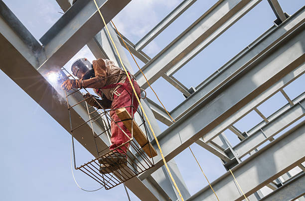Welding metal columns Welder soldering metal girders in a structure high above safety harness stock pictures, royalty-free photos & images