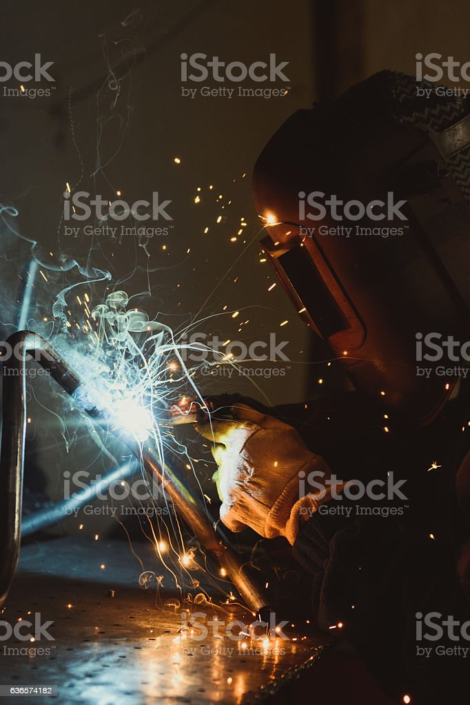 Welding metal with a flash of hot sparks on a work table, in an...