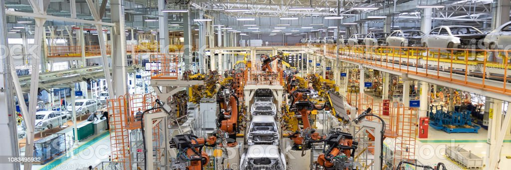 Assembly line production of new car. Automated welding of car body on...