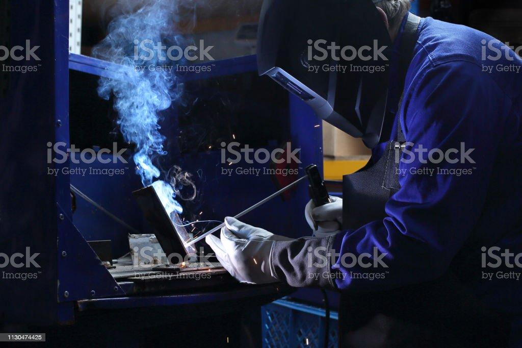 Welder\'s workshop. The man is welding in the workshop.