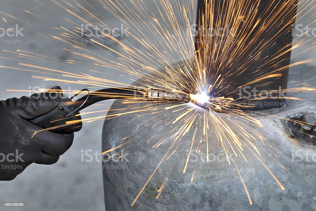 Arc welding of a steel, welder hands in gloves, tool and sparks