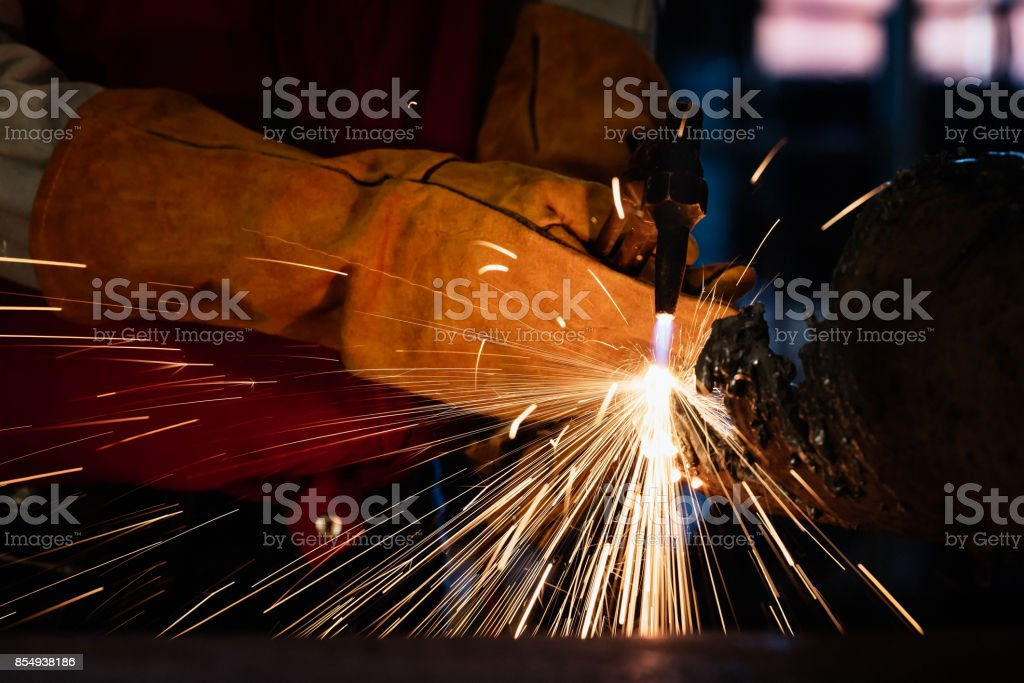 Closeup of industrial worker at the factory welding with protective...