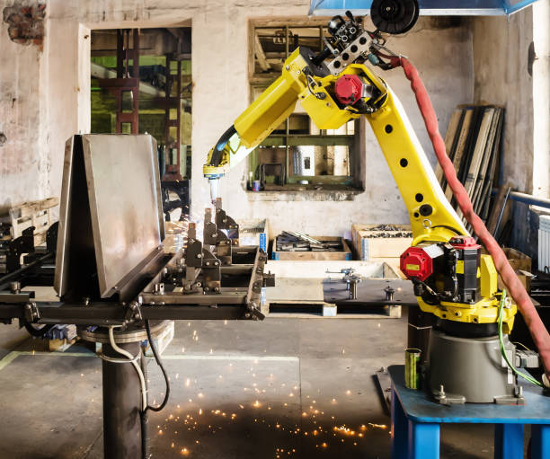 Welding robot in operation Photo taken in Russia, in factory premises mechanical engineering stock pictures, royalty-free photos & images