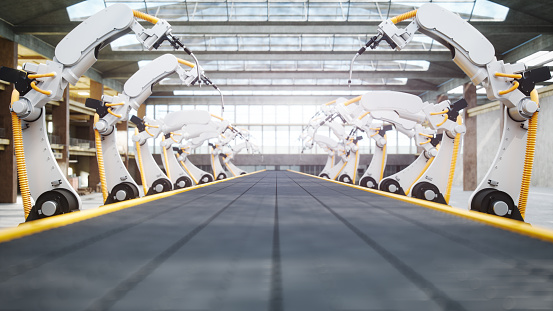 Interior of a modern automated factory with robotic arms and conveyor belt.