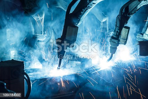 istock Welding robots movement in a car factory 1054184002