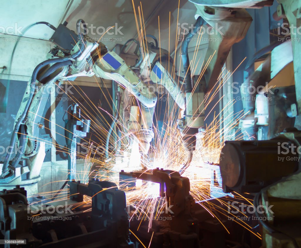 Welding robots movement in a car factory. stock photo