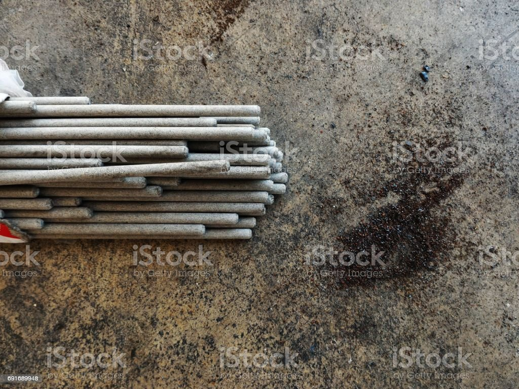 welding rod and metal dust on dirty ground stock photo