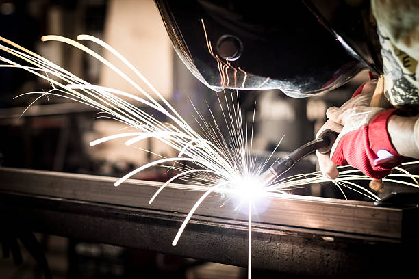 Welding steel Worker welding steel in company. metalwork stock pictures, royalty-free photos & images