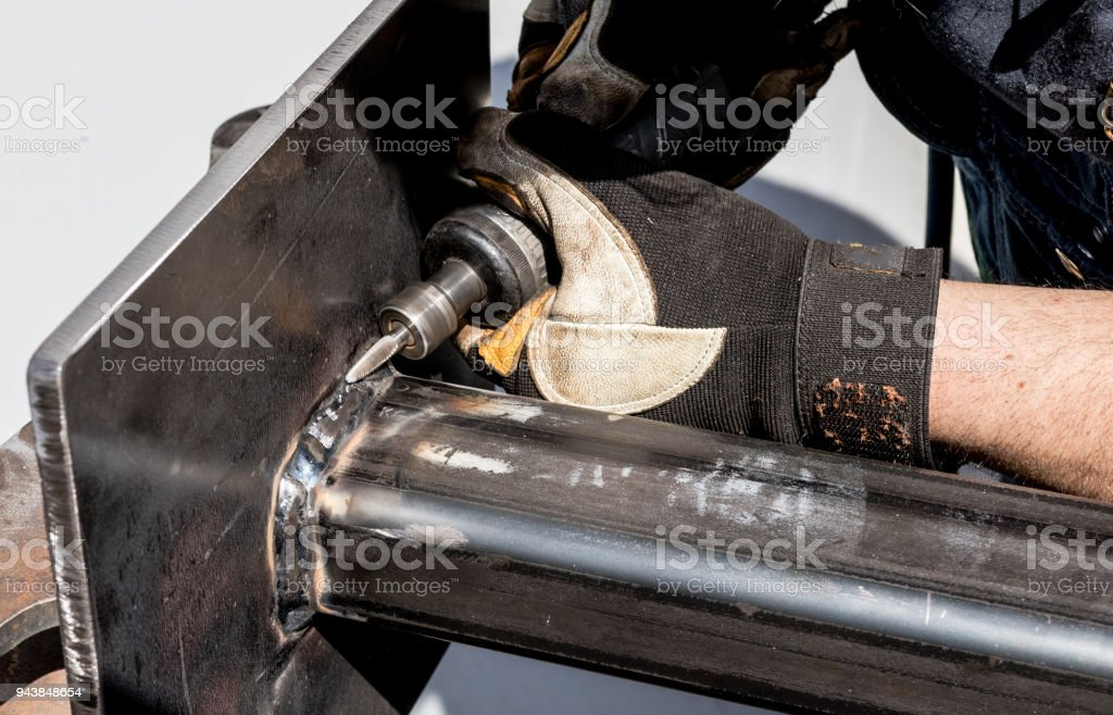 Welding steel worker breaking away slag from perfect spiral welds beads stock photo
