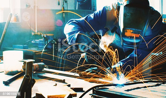 Unrecognizable man welding metal plate and construction frame. This is arc welding.The worker is using protective mask and blue working uniform. Background is lit orange. Long exposure. Toned image.