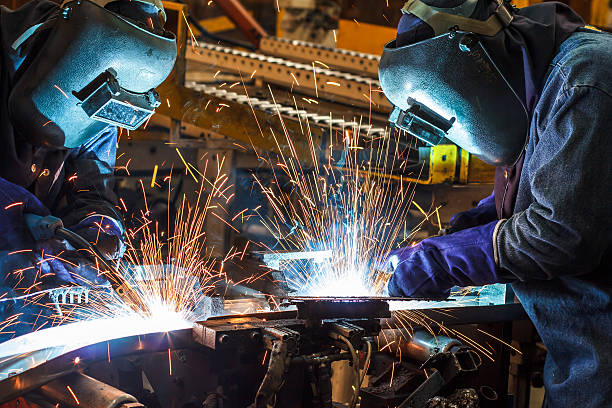 welding with sparks - manufacturing occupation stock photos and pictures