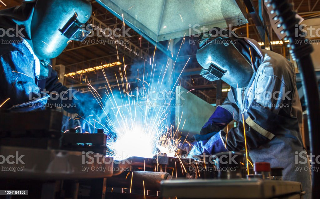worker with protective mask welding metal industrial