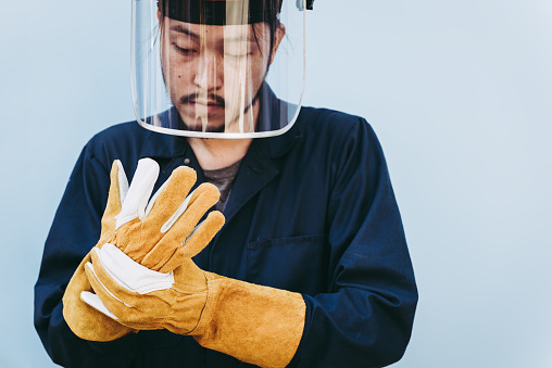 Welding Worker Wear Personal Safety Equipment Protective Concept, Portrait of Mechanical Handyman Standing While Wearing Safety Leather Gloves and Face Shield Before Metal Welding Work in Workshop.