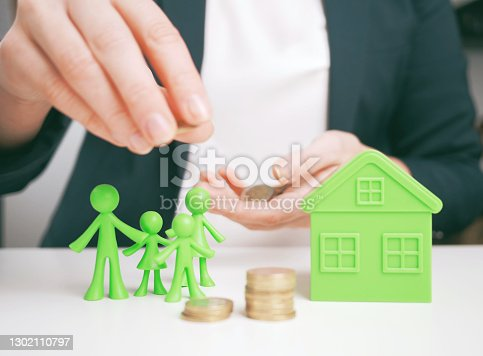 istock welfare benefits koncept. Hands of woman making a gesture of protection over family and home with piggy bank. House construction and savings insurance concept. Property insurance and security concept. 1302110797