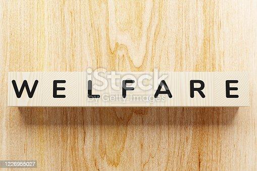 Welfare word written on cube shape wooden blocks on wooden background.