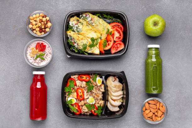 Well balanced lunch for two, concept Healthy well balnced food. Plastic boxes with fresh meal, almond, hazelnut, tomato juices, apple, yogurt with chia seeds on wooden table, top view, concept food state stock pictures, royalty-free photos & images