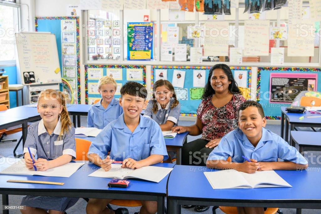 Well behaved school children sitting at their desks with their teacher stock photo