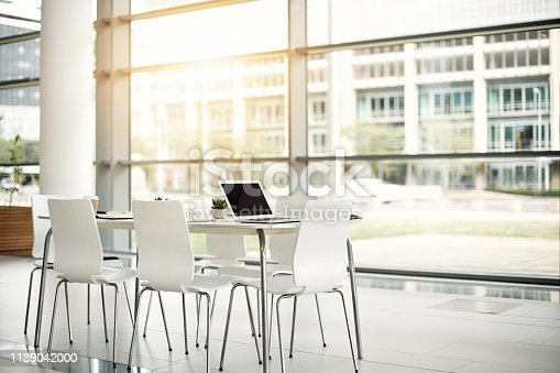 Still life shot of an office space furnished with a table and chairs