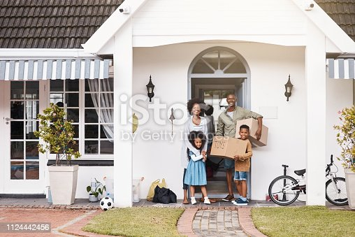 Portrait of a happy family standing in front of their new home