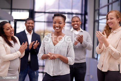 Shot of a young businesswoman being applauded by her colleagues in a modern office