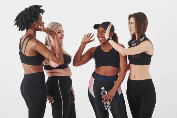 Well done, after workout. Group of multi ethnic women standing in the studio against white background stock photo