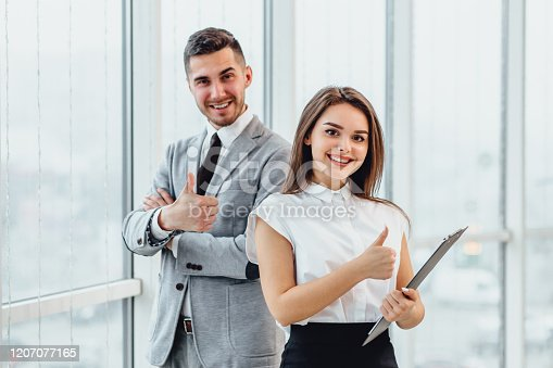 488279375 istock photo Well Done Man and woman giving thumbs up, saying that the goal is successfully achieved. 1207077165