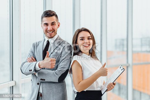 488279375 istock photo Well Done Man and woman giving thumbs up, saying that the goal is successfully achieved. 1207077652