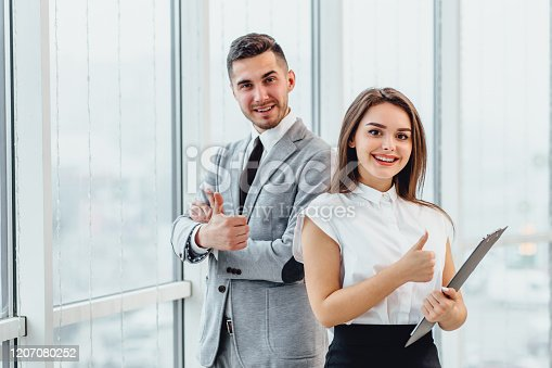 488279375 istock photo Well Done Man and woman giving thumbs up, saying that the goal is successfully achieved. 1207080252