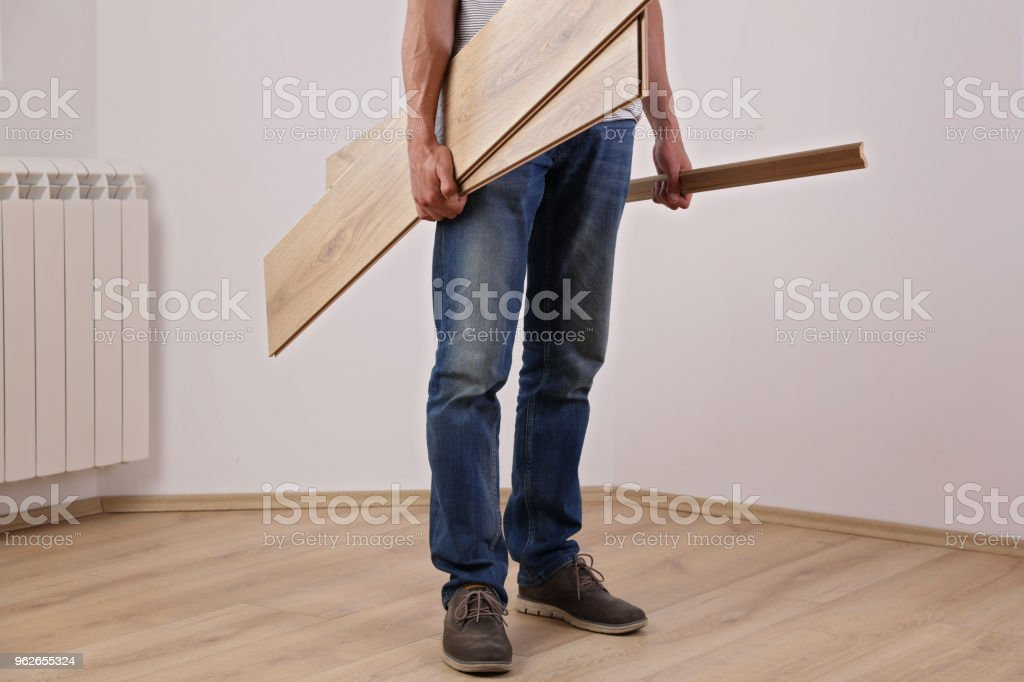 Well done. Man finished new laminate wooden flooring installing stock photo